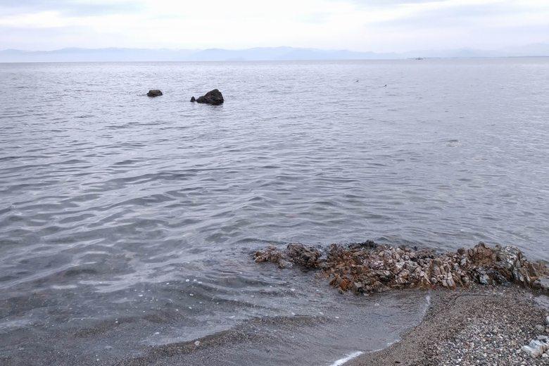 砂利浜の水辺に見える岩